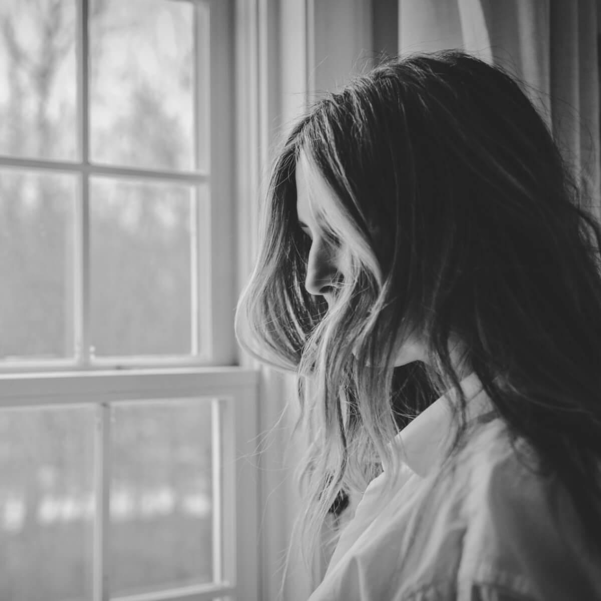mujer viendo hacia la ventana